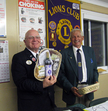 Lion District Governor John Haak receives a gift from Barker